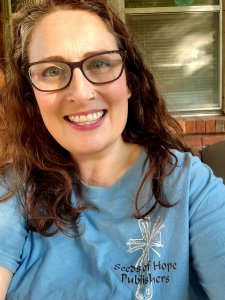 """A middle-aged Caucasian woman with long dark brown hair and glasses is smiling at the camera. She is a wearing a light blue T-shirt with a logo on her right shoulder. It is a customized cross with a shaft of wheat. The words """"Seeds of Hope Publishers"""" is written across it."""